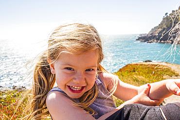 Wind blowing hair of smiling Caucasian girl near ocean