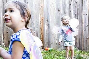 Curious girls wearing fairy wings in backyard