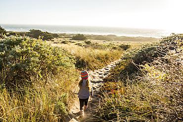 Caucasian girl walking on sandy path