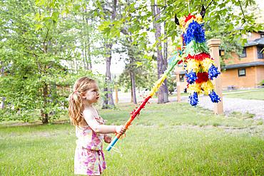 Caucasian girl hitting pinata outdoors