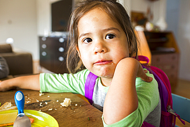 Messy mixed race girl eating food and wearing backpack at table