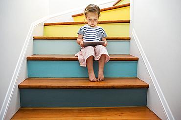 Caucasian girl using digital tablet on staircase