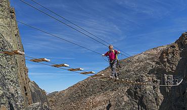 Caucasian man crossing rope bridge on mountain