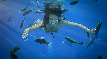 Asian woman swimming underwater with fish
