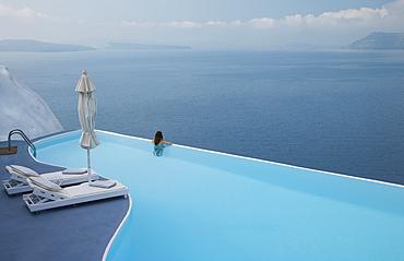Caucasian woman in infinity pool admiring scenic view of ocean