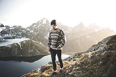 Caucasian man carrying camera near mountain lake