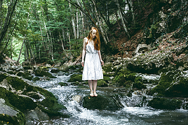 Caucasian woman standing on rock in river