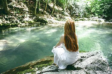 Caucasian woman sitting near river