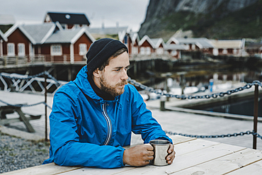 Pensive Caucasian man drinking coffee at table at waterfront