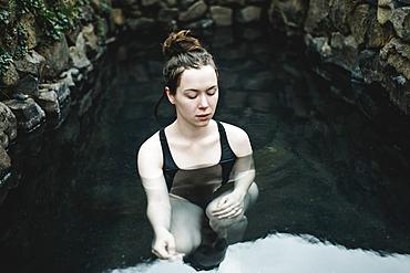 Caucasian woman swimming in pond