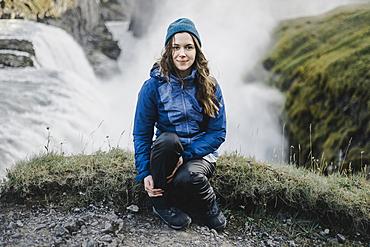 Portrait of smiling Caucasian woman sitting near waterfall