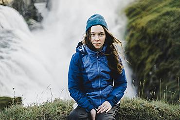 Portrait of serious Caucasian woman sitting near waterfall