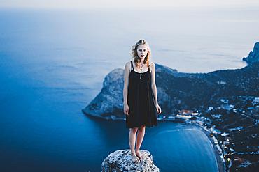 Caucasian woman standing on rock near ocean