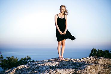 Wind blowing dress of Caucasian woman standing on rock near ocean