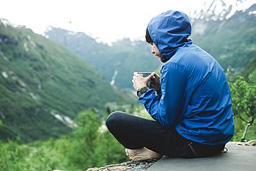 Caucasian man sitting in mountain landscape drinking coffee