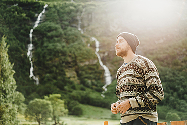 Pensive Caucasian man wearing sweater and hat outdoors