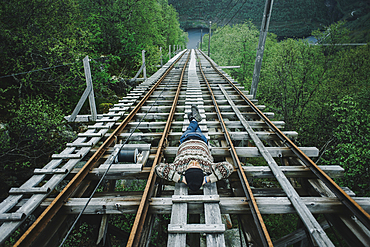 Caucasian man laying on train tracks