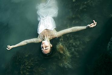 Caucasian woman wearing dress floating in water