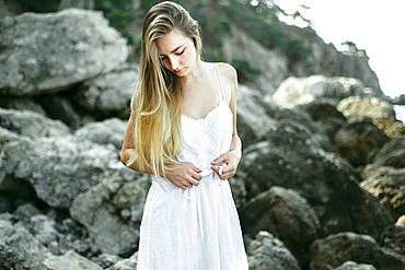 Caucasian woman wearing dress standing on the rocks