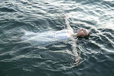 Caucasian woman wearing a dress floating in water