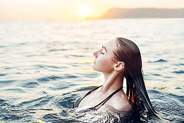 Caucasian woman swimming at sunset