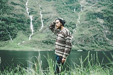 Pensive Caucasian man standing near river