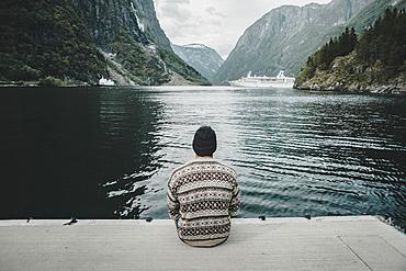 Caucasian man sitting on dock watching cruise ship