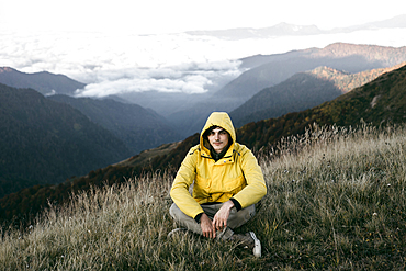 Caucasian man sitting in remote mountain landscape