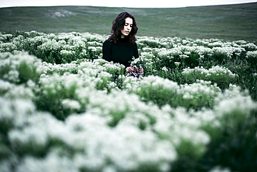 Caucasian woman standing in the field of wildflowers