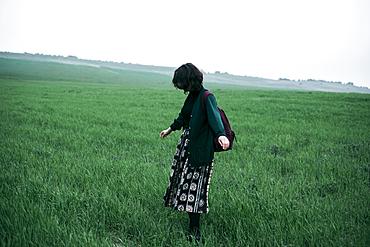 Caucasian woman standing in field of grass