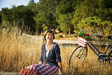 Laughing Caucasian woman sitting near bicycle