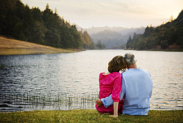 Couple sitting in grass and hugging near river