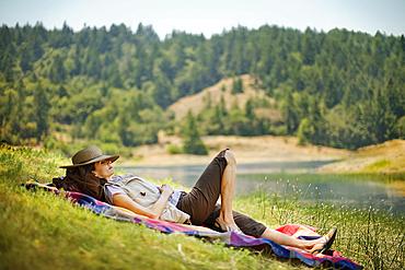 Hispanic woman relaxing on blanket near river