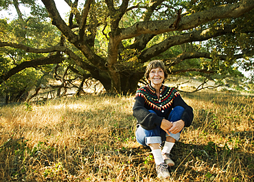 Smiling Caucasian woman sitting near tree