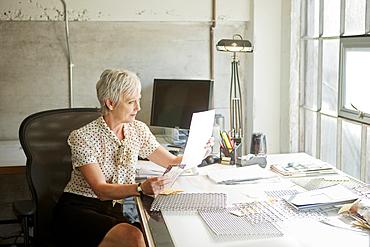 Caucasian businesswoman reading paperwork in office