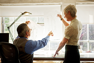 Architects examining blueprint in office