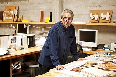 Portrait of serious Hispanic designer examining color swatches in office