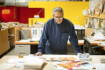 Serious Hispanic designer examining color swatches in office