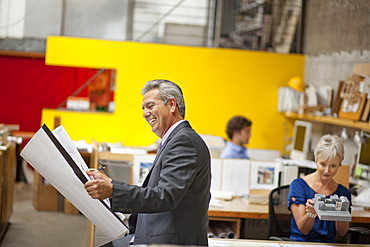Smiling architect reading blueprint in office