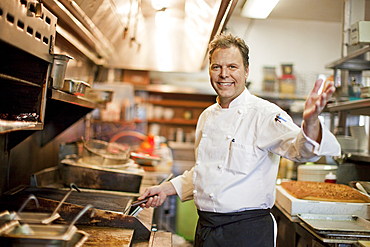 Portrait of Caucasian chef waving in restaurant kitchen