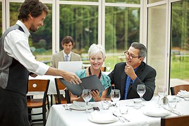 Waiter presenting menu to couple in restaurant