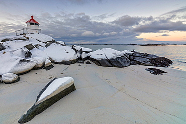 Colorful arctic sunset on the lighthouse surrounded by snow and icy sand, Eggum, Vestvagoy (Vest-Vagoy) Island, Lofoten Islands, Arctic, Norway, Scandinavia, Europe