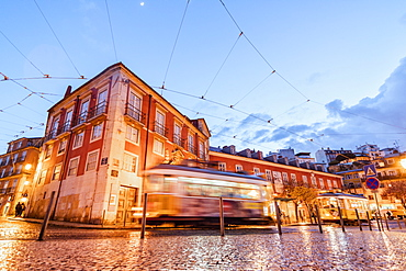 City lights on the typical architecture and old streets at dusk while the tram 28 proceeds, Alfama, Lisbon, Portugal, Europe