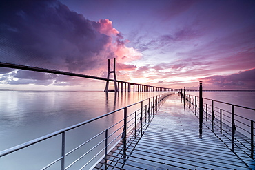 Sunrise colors the clouds reflected in Tagus River and frame the Vasco da Gama bridge in Lisbon, Portugal, Europe