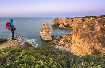 The photographer admires cliffs and ocean of Praia da Marinha at dawn, Caramujeira, Lagoa Municipality, Algarve, Portugal, Europe