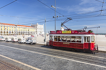 A typical red tram stops at the historical Praca Do Comercio square near the Tagus river, Lisbon, Estremadura, Portugal, Europe