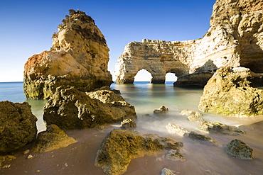 Sunrise on the cliffs and turquoise water of the ocean, Praia da Marinha, Caramujeira, Lagoa Municipality, Algarve, Portugal, Europe