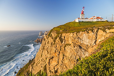 The Cabo da Roca lighthouse overlooks the promontory towards the Atlantic Ocean at sunset, Sintra, Portugal, Europe
