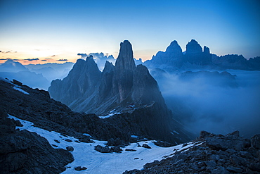 The Cadini di Misurina emerging from the fog after sunset, in a typical Dolomitic landscape, Dolomites, South Tyrol, Italy, Europe