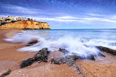 Ocean waves crashing on rocks and beach surrounding Carvoeiro village at sunset, Lagoa Municipality, Algarve, Portugal, Europe